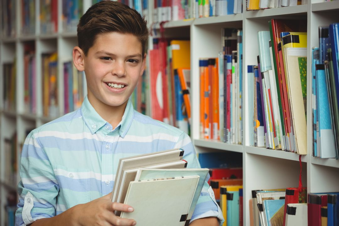 Portrait of schoolboy holding books in library at school Free Stock Images from PikWizard