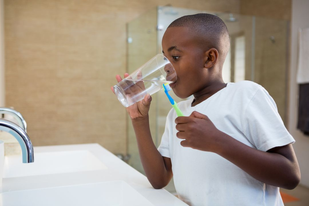 Boy drinking water from glass while standing by sink Free Stock Images from PikWizard