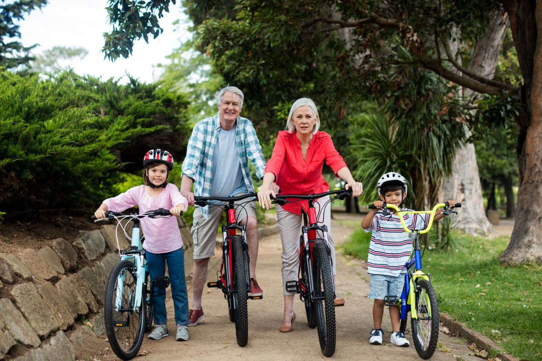 Portrait of multi-generation family standing with bicycle in park on a sunny day Free Stock Images from PikWizard