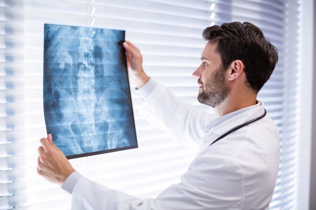 Male doctor examining x-ray in clinic Free Stock Images from PikWizard