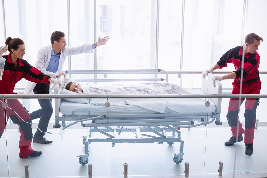 Doctors pushing emergency stretcher bed in corridor at hospital Free Stock Images from PikWizard