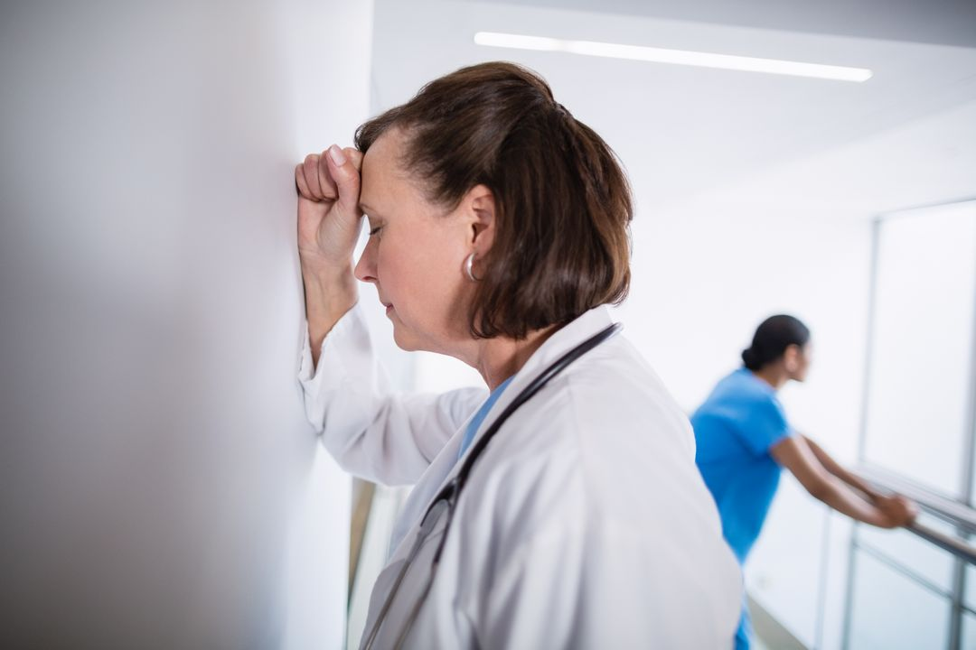 Depressed doctor leaning against wall at hospital corridor Free Stock Images from PikWizard