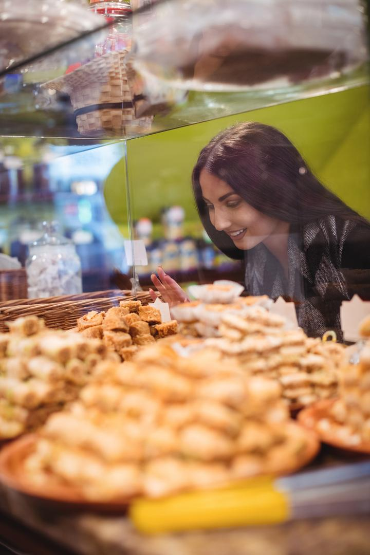 Beautiful woman looking at turkish sweets on display in shop
