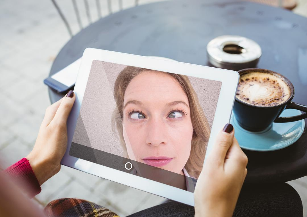 Woman making funny faces while taking selfie on digital tablet at cafe Free Stock Images from PikWizard