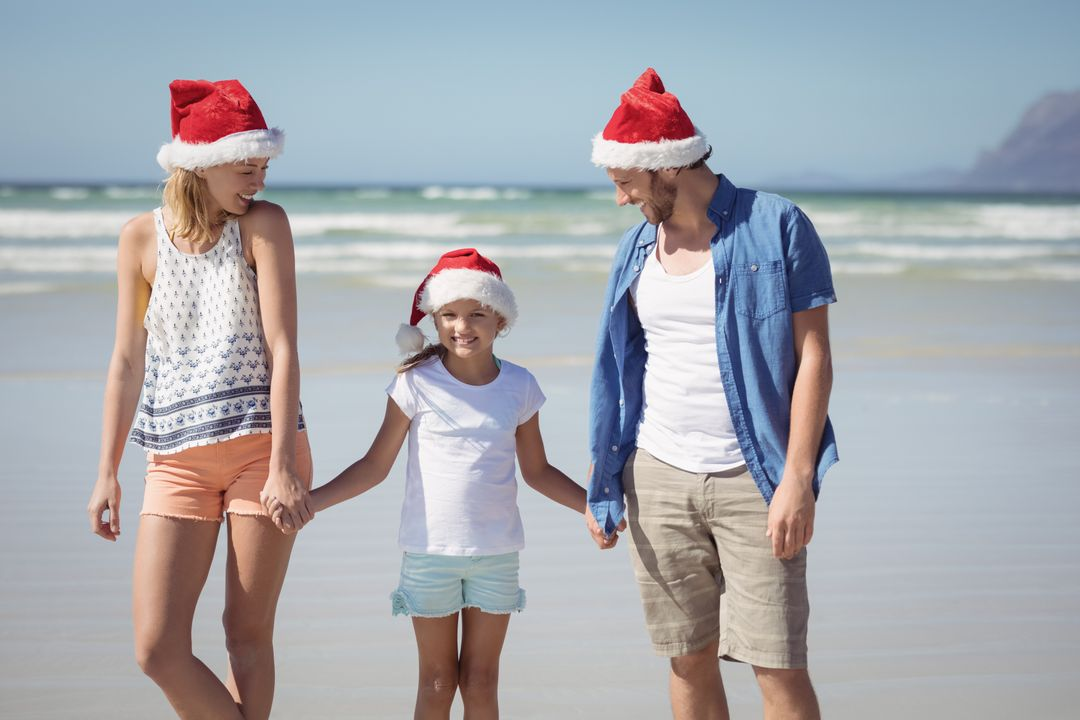 Happy family wearing Santa hat while standing at beach during sunny day Free Stock Images from PikWizard