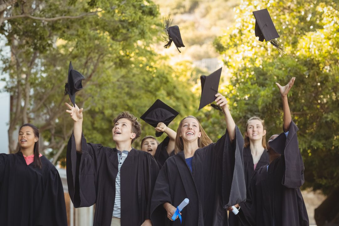 Successful graduate school kids throwing mortarboard in air in campus at school Free Stock Images from PikWizard