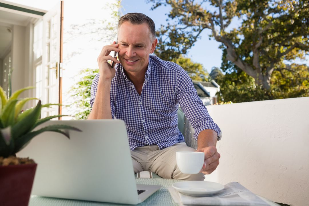 Smiling mature businessman talking on phone while having coffee in outdoor cafe Free Stock Images from PikWizard
