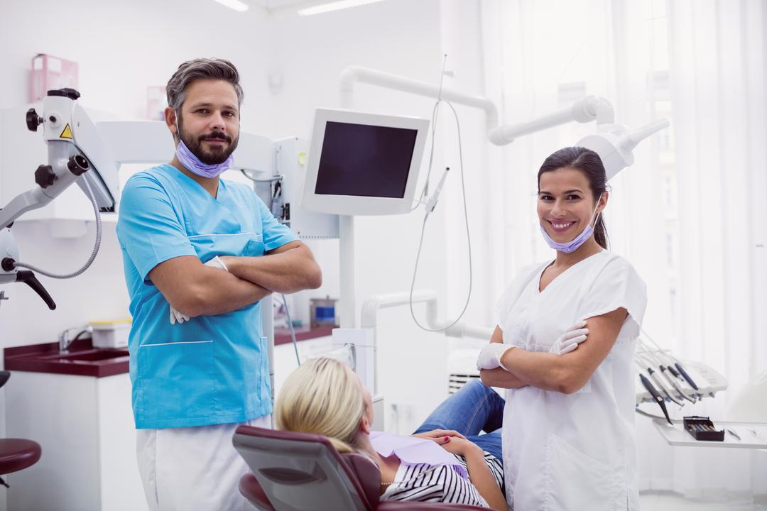 Portrait of male and female dentist standing with arms crossed in dental clinic Free Stock Images from PikWizard