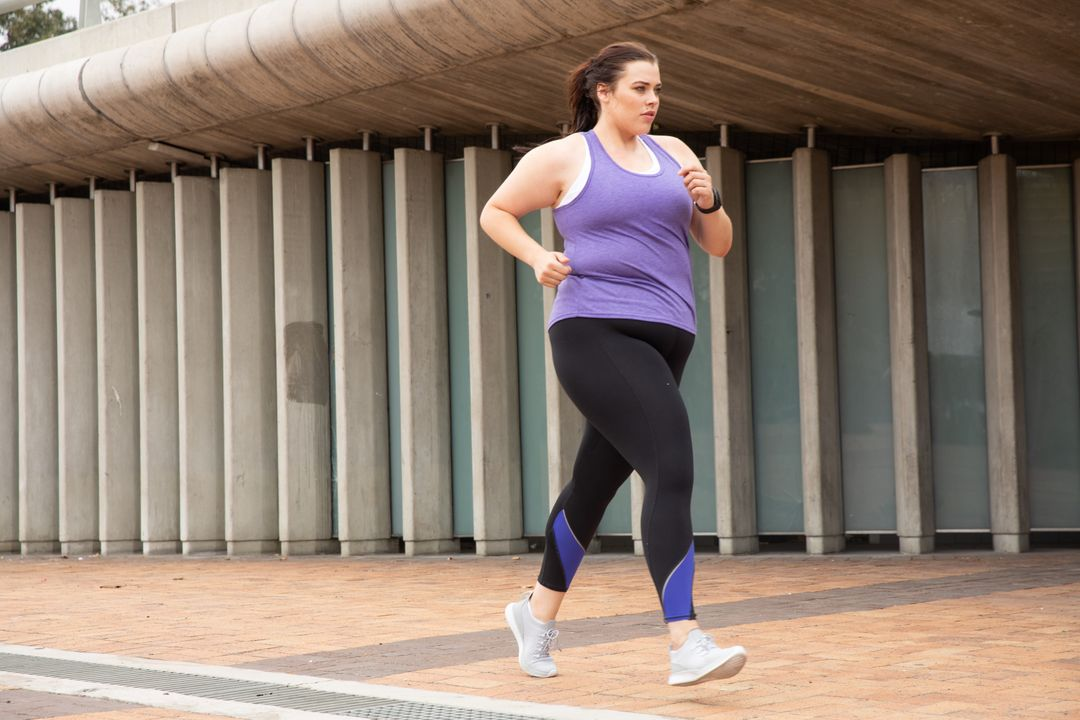 Curvy Caucasian woman with long dark hair wearing sports clothes exercising in a city, running past modern architecture in an urban pedestrian area