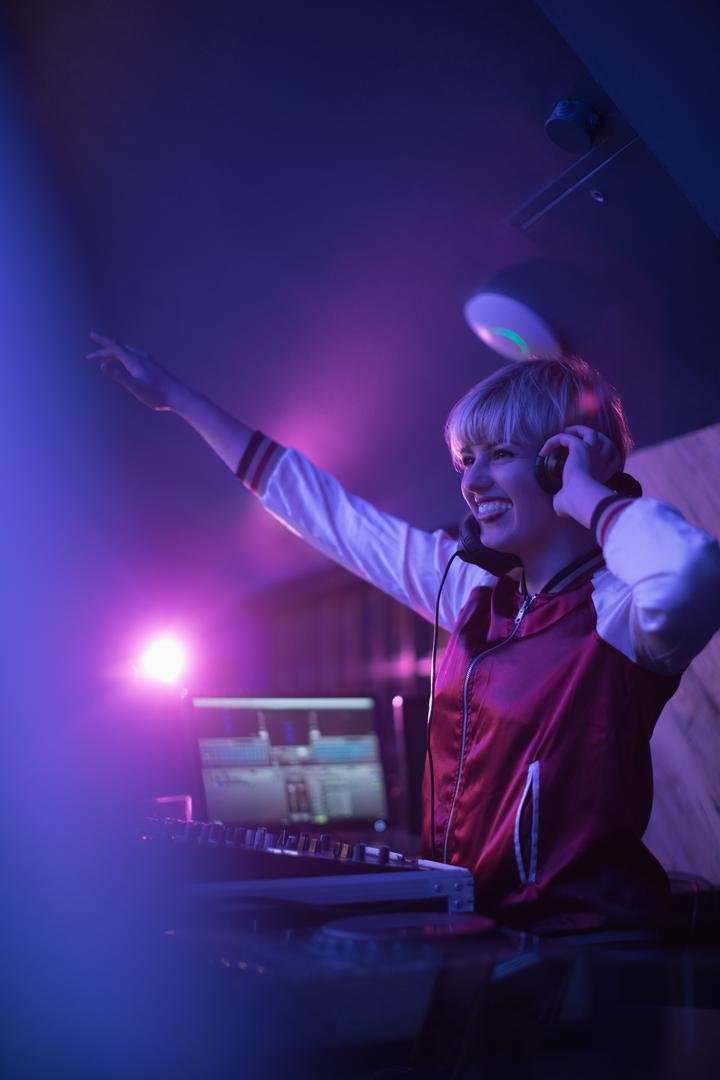Pretty female dj waving her hand while playing music in bar Free Stock Images from PikWizard