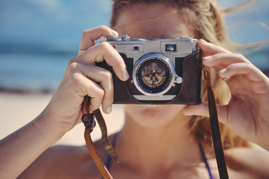 Close up of a woman holding a camera up over her face, taking a photo on a beach