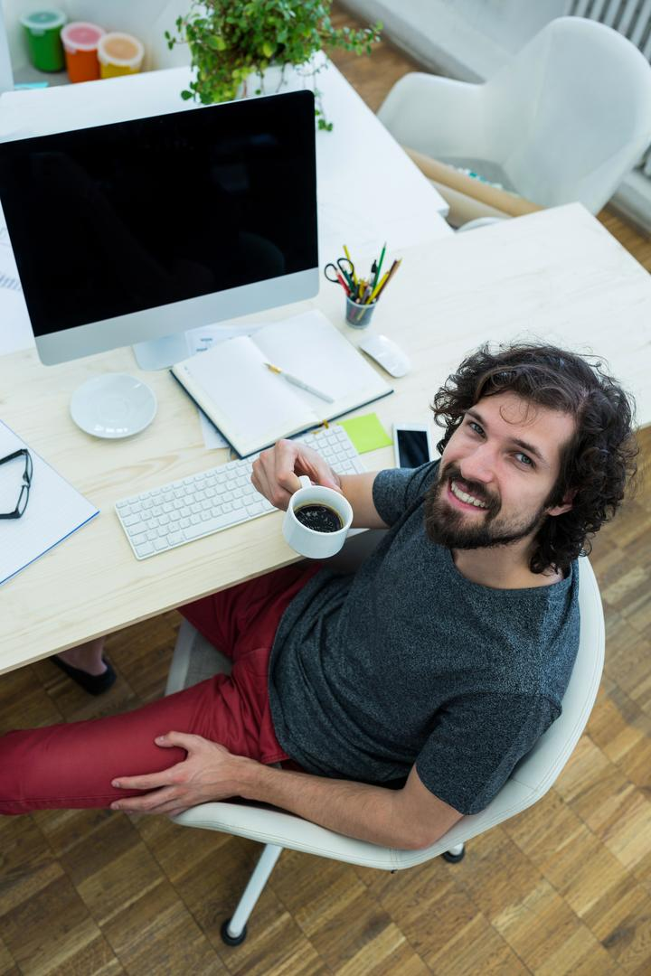 Male graphic designer having black coffee in office