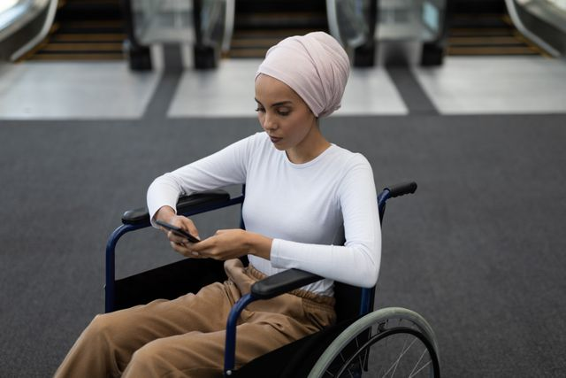 Side view of Disabled young mixed-race female executive using mobile phone in the lobby at office
