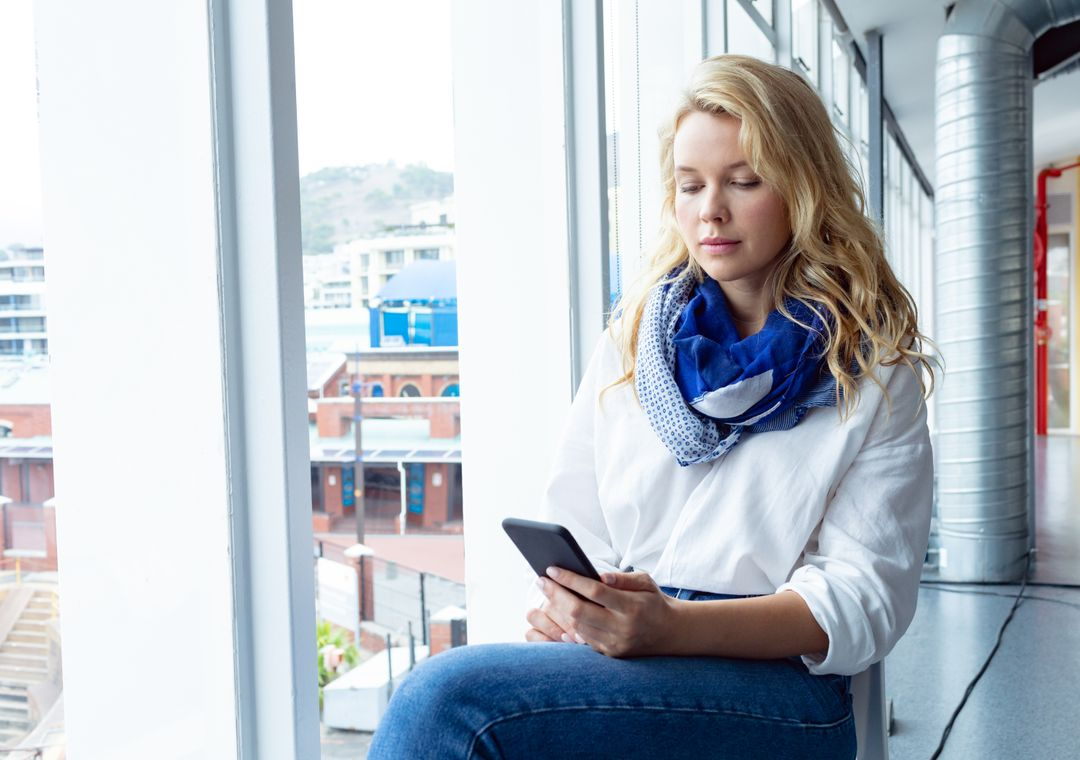 Front view of beautiful young Caucasian businesswoman using mobile phone near window in a modern office