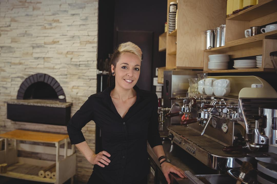 Portrait of woman standing in kitchen at café