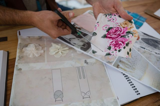 Cropped hands of designer cutting papers at table