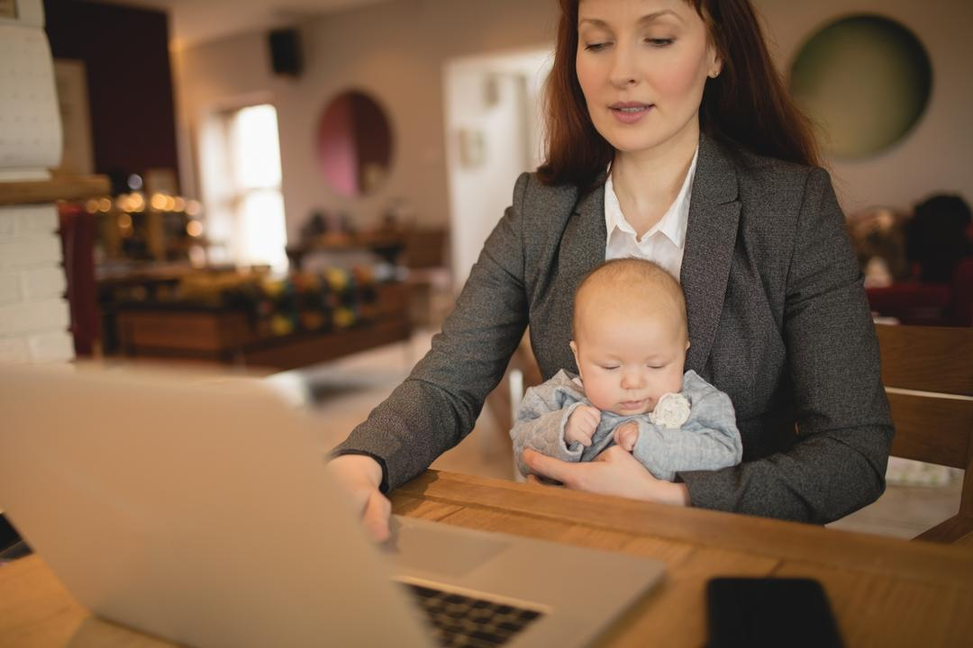 Mother using laptop while holding her baby at  home