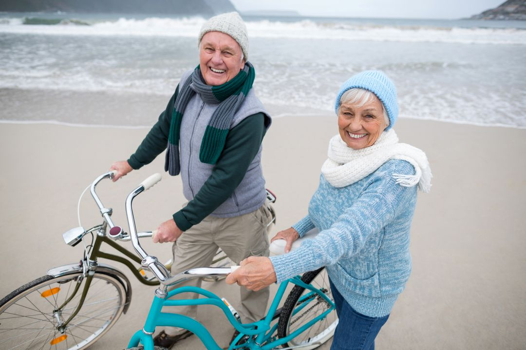 Portrait of happy senior couple standing with bicycles on the beach  Free Stock Images from PikWizard