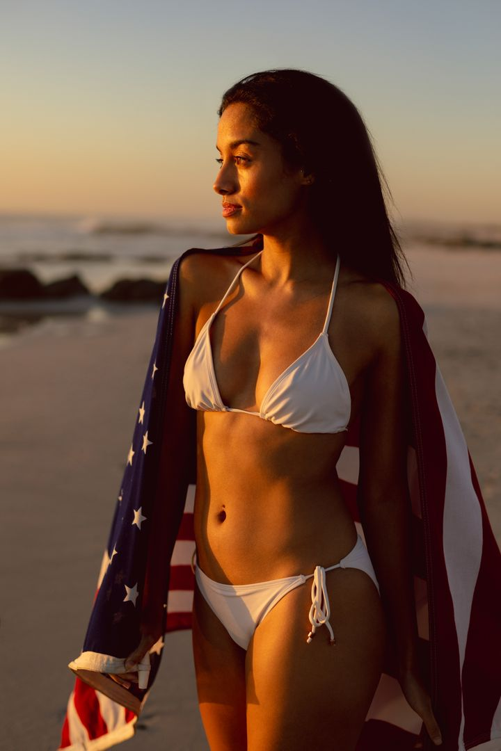 Beautiful woman with an American flag standing on the beach