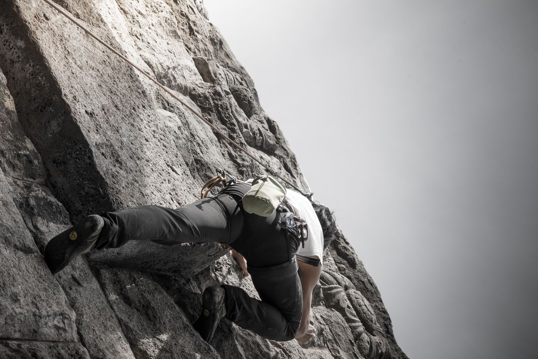 Image of a fitness man rock climbing up a mountain side