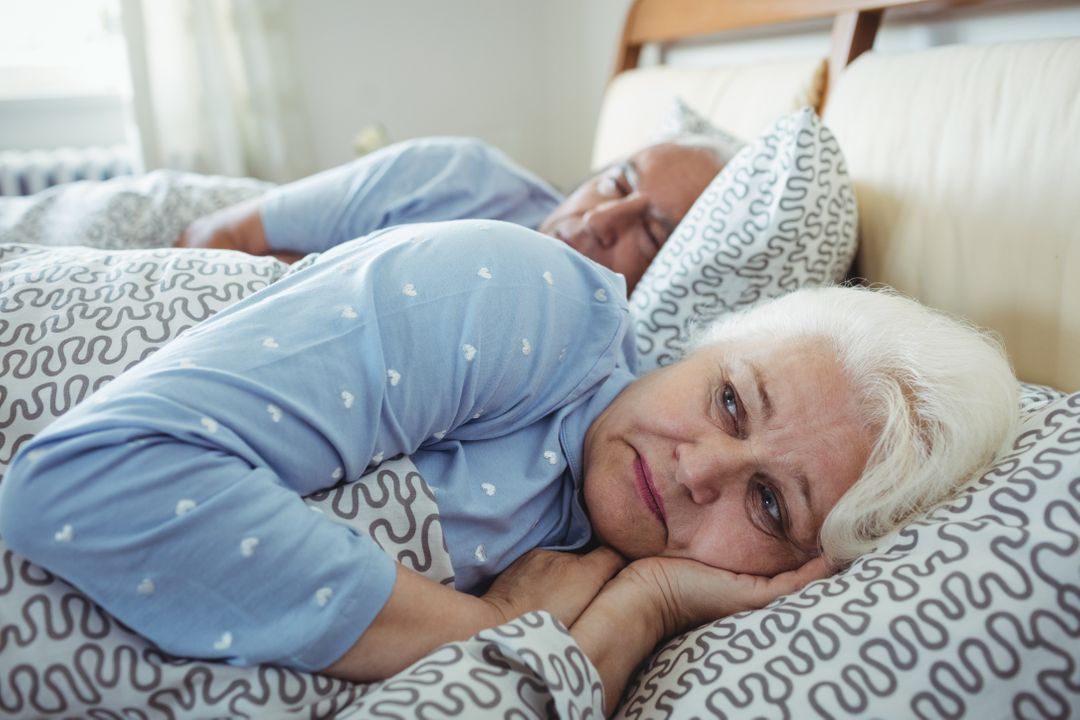 Senior man sleeping while woman still awake on bed in bed room Free Stock Images from PikWizard