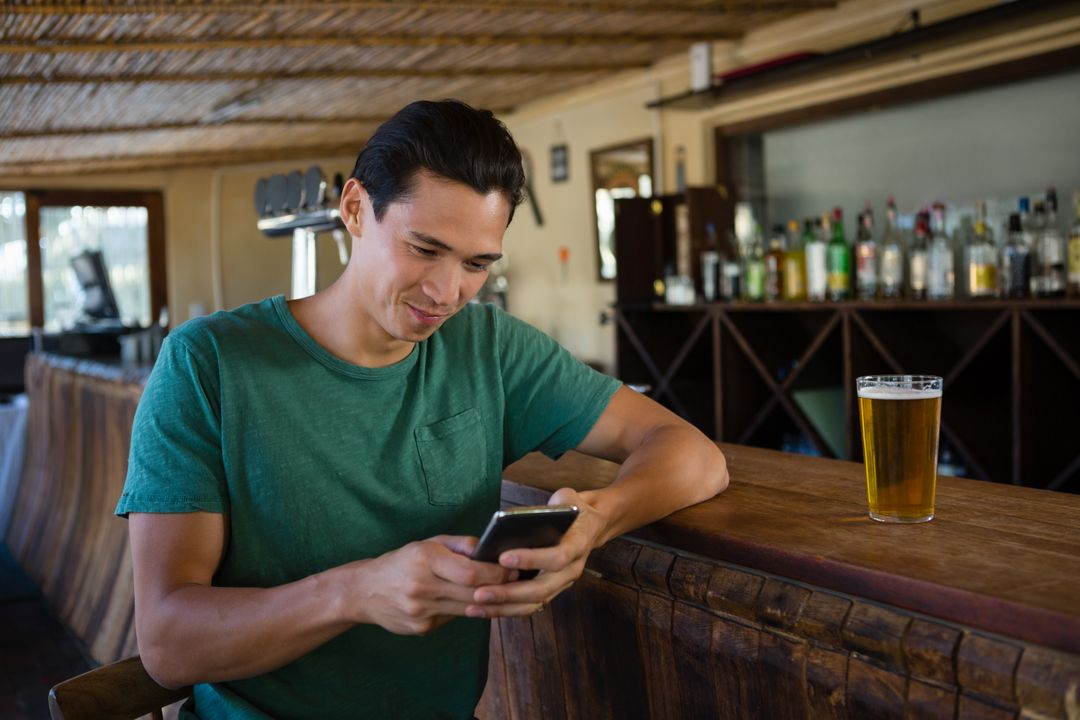 Young man using phone while sitting at counter in restaurant Free Stock Images from PikWizard