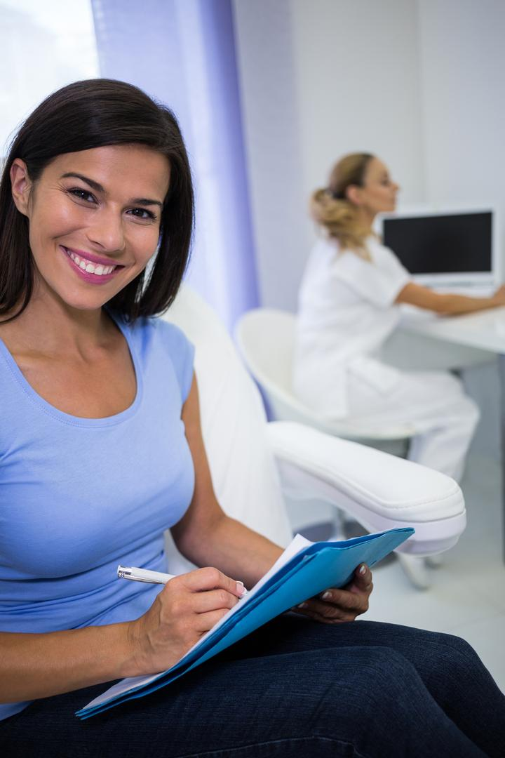 Portrait of smiling female patient writing on a medical file Free Stock Images from PikWizard