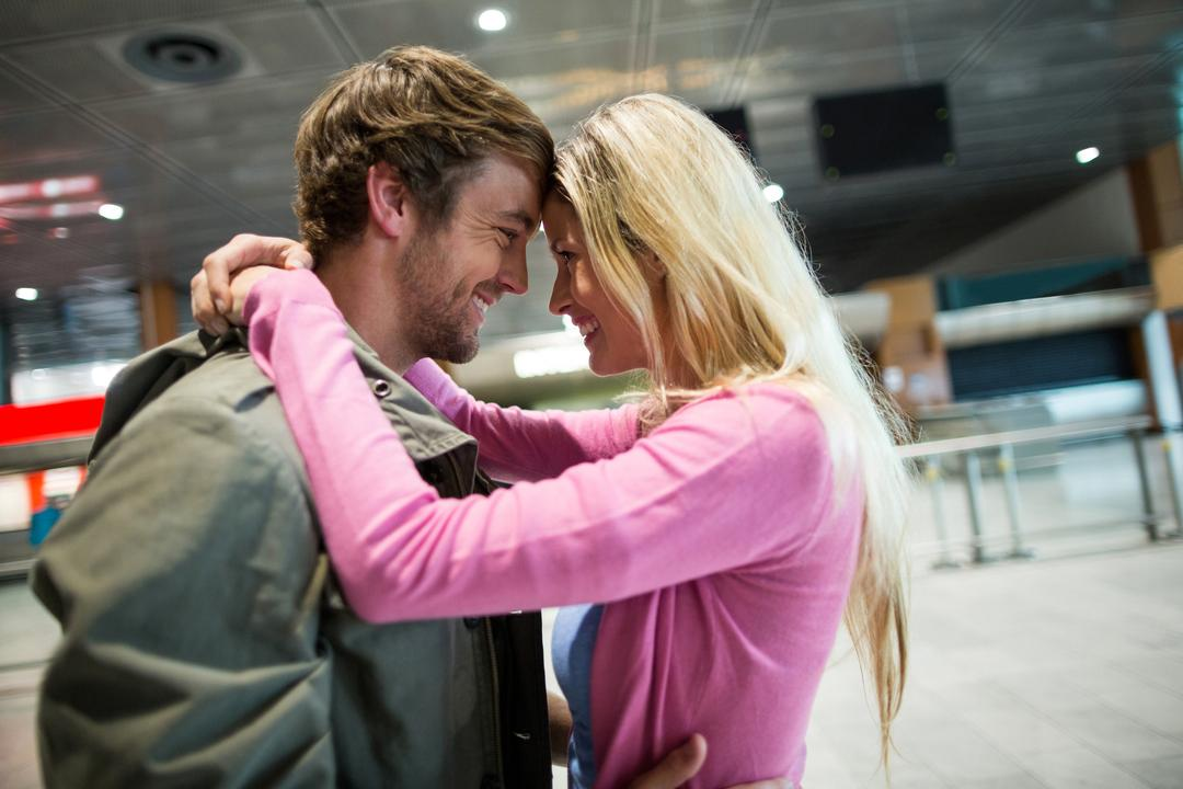 Cheerful couple embracing each other in waiting area at airport terminal