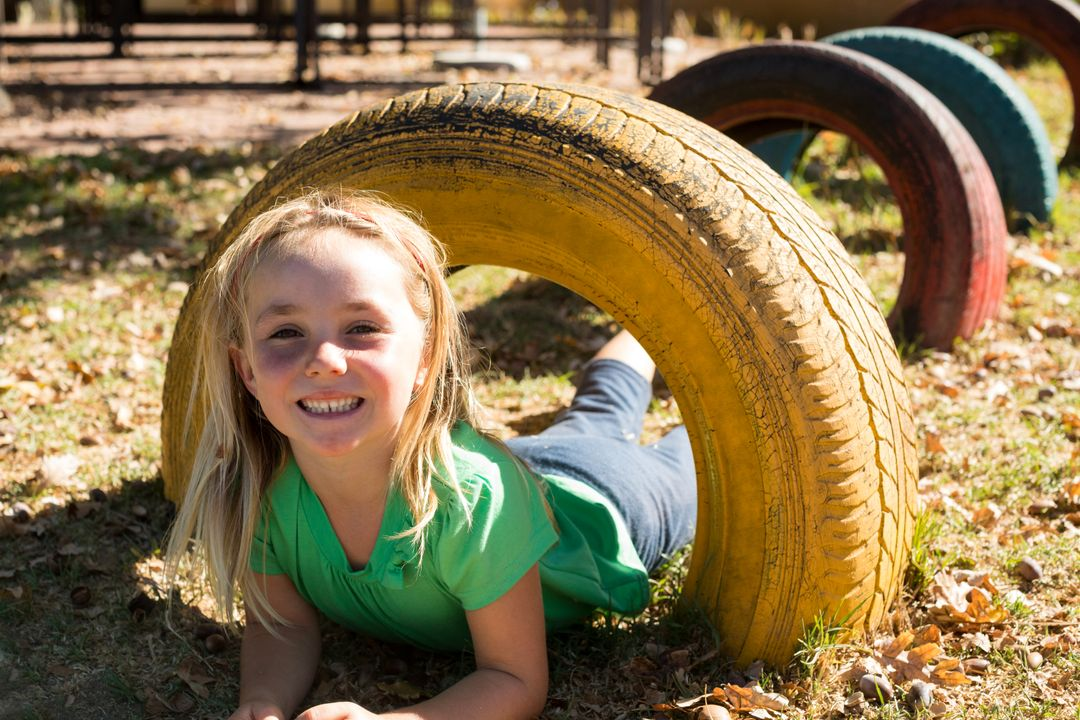 Portrait of happy girl playing with tire at playground Free Stock Images from PikWizard