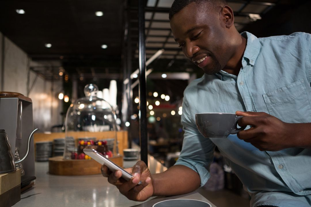 Man using mobile phone while having coffee in restaurant Free Stock Images from PikWizard