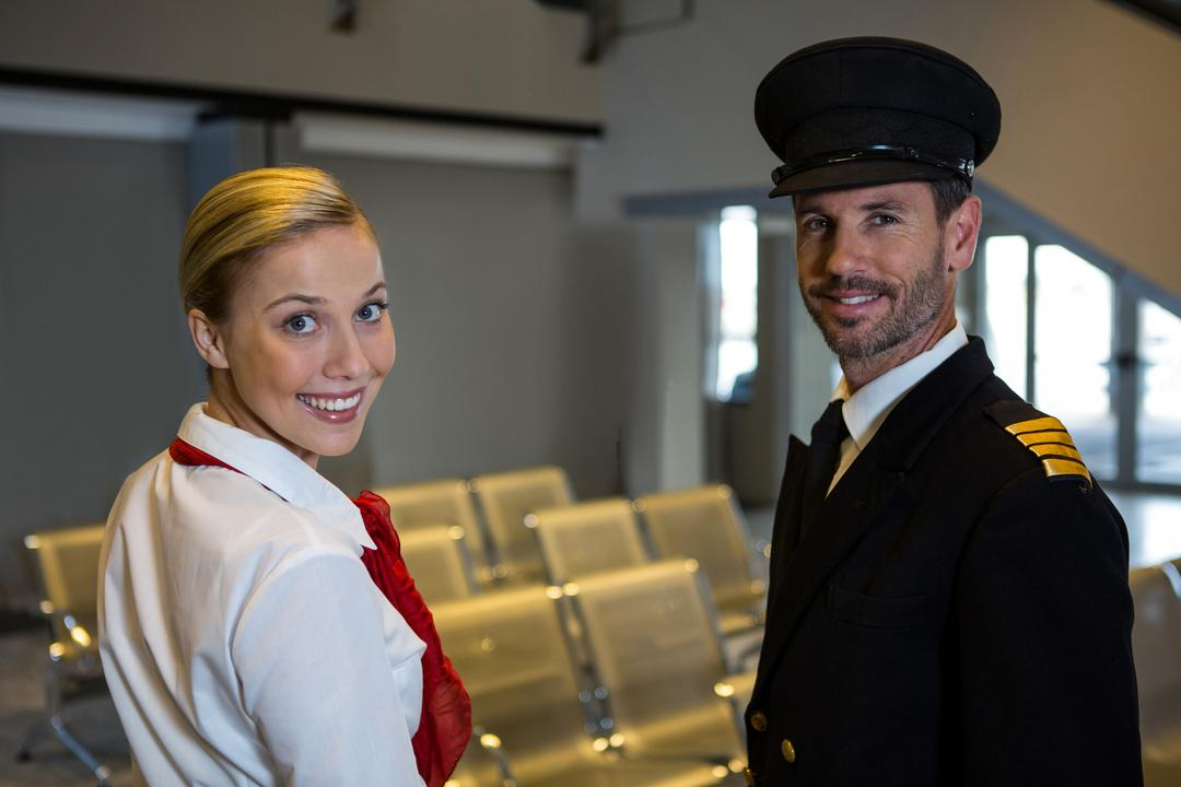 Portrait of happy pilot and air hostess standing in the airport terminal