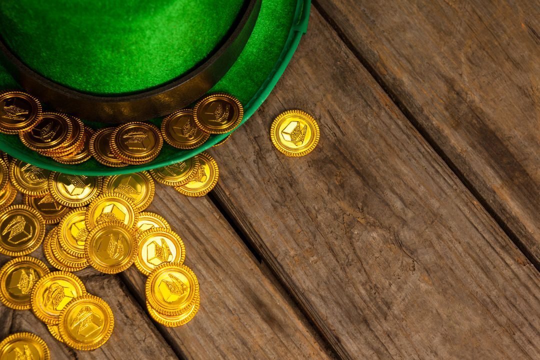 St Patricks Day leprechaun hat with gold chocolate coins on wooden background