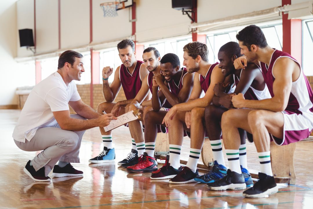 Coach explaining game plan to basketball players in the court Free Stock Images from PikWizard