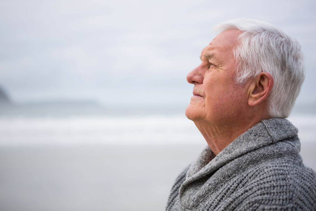 Thoughtful senior man standing at the beach Free Stock Images from PikWizard