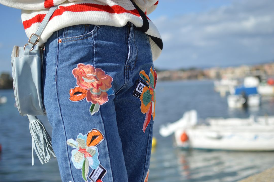Woman standing with colourful embroidered jeans