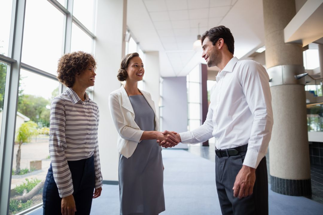 Business executives shaking hands with each other at conference centre