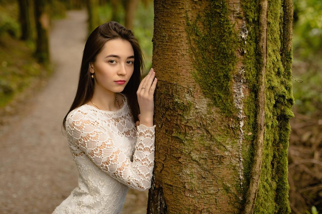 Portrait of woman posing on tree trunk at forest