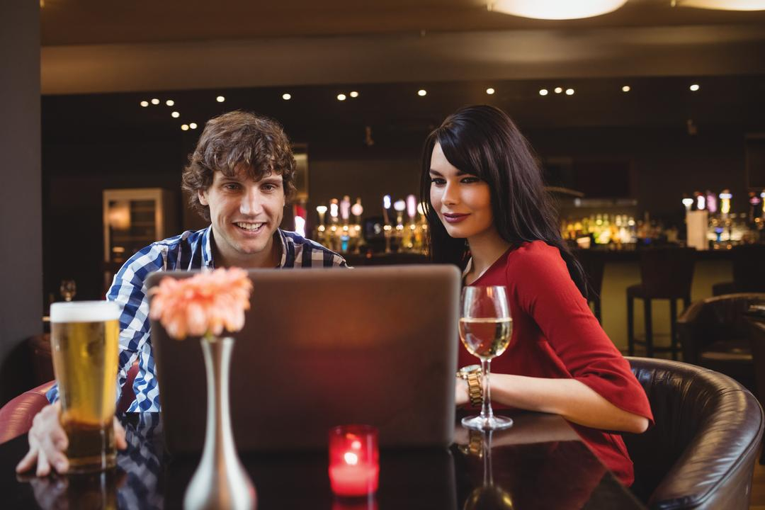 Couple using laptop while having drinks in bar