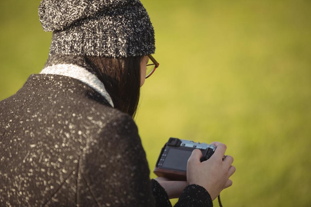 Over the shoulder image of a woman looking at photos on a camera