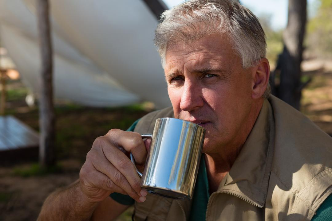 Portrait of mature man drinking coffee at campsite