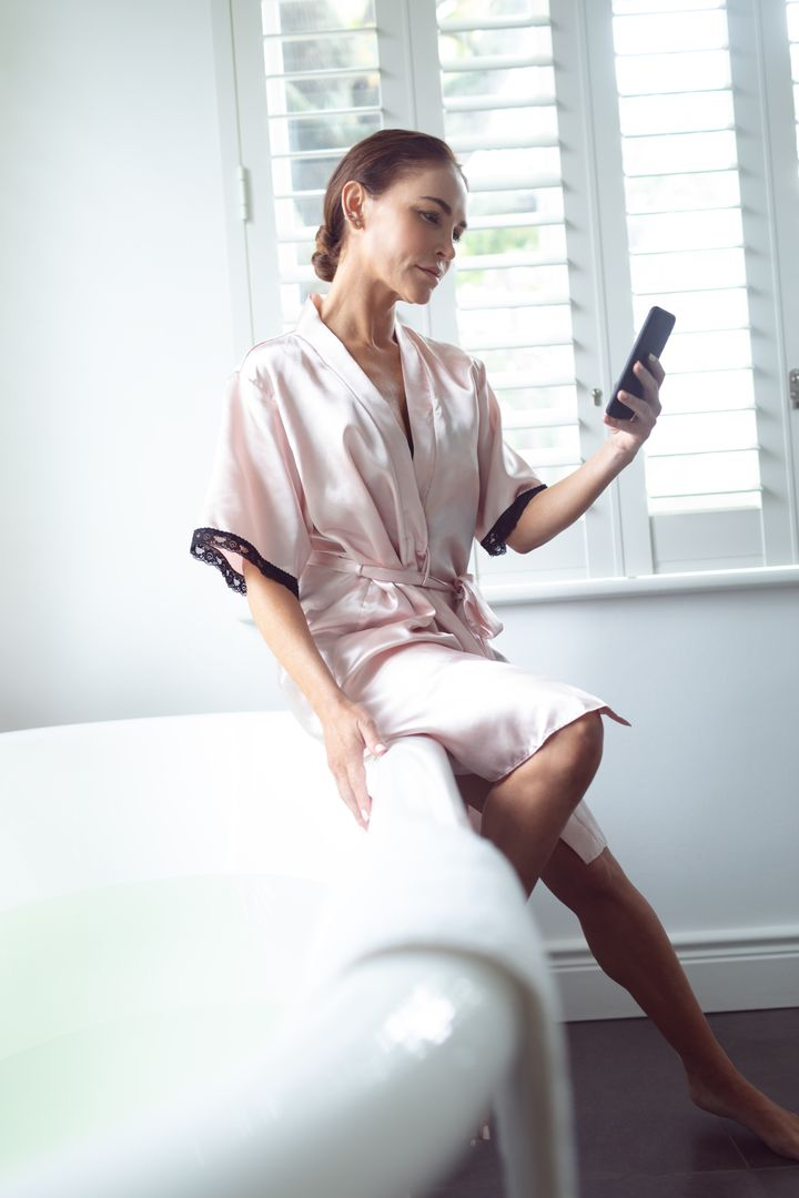 Woman using mobile phone while sitting on the edge of bathtub in bathroom at home