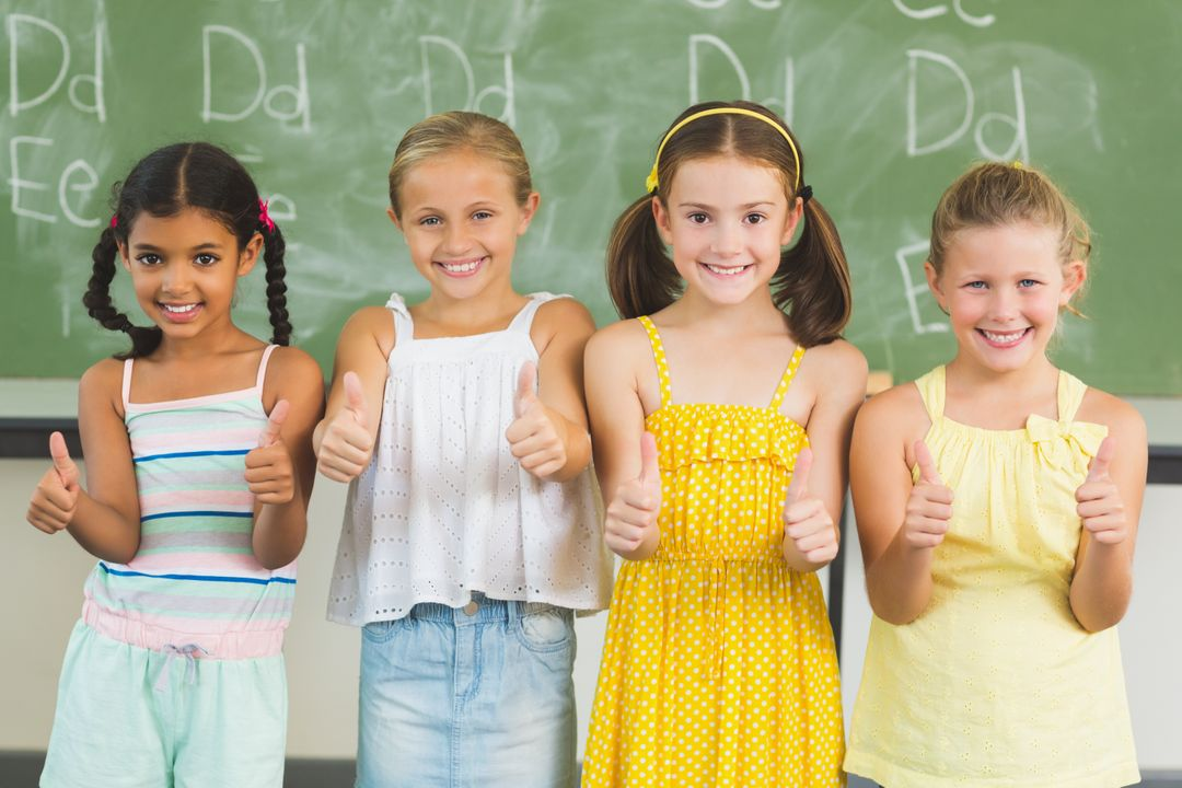 Portrait of smiling kids showing thumbs up in classroom at school Free Stock Images from PikWizard