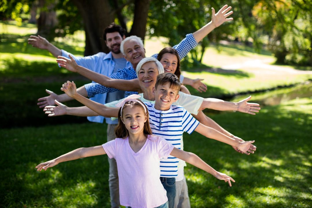 Multi generation family standing in a row with arms outstretched at park