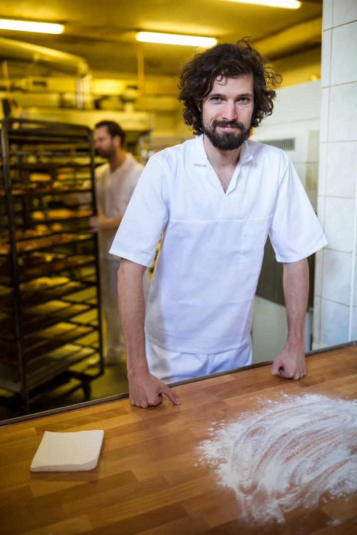 Portrait of smiling baker standing at work counter in bakery