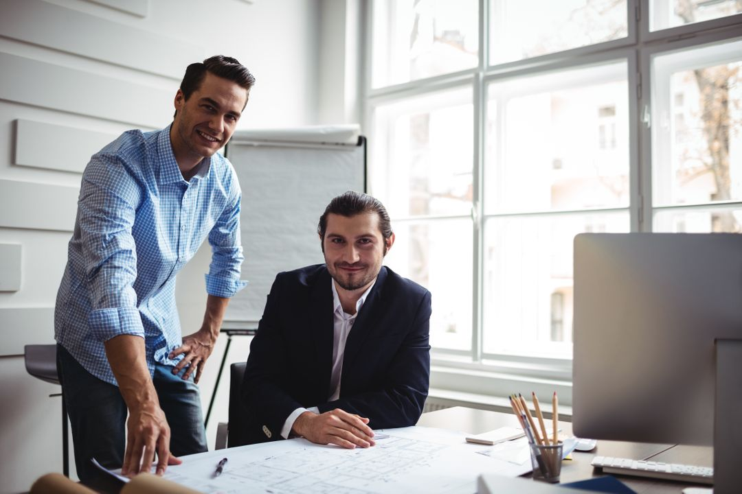 Portrait of smiling interior designer with coworker working on blueprint in office Free Stock Images from PikWizard