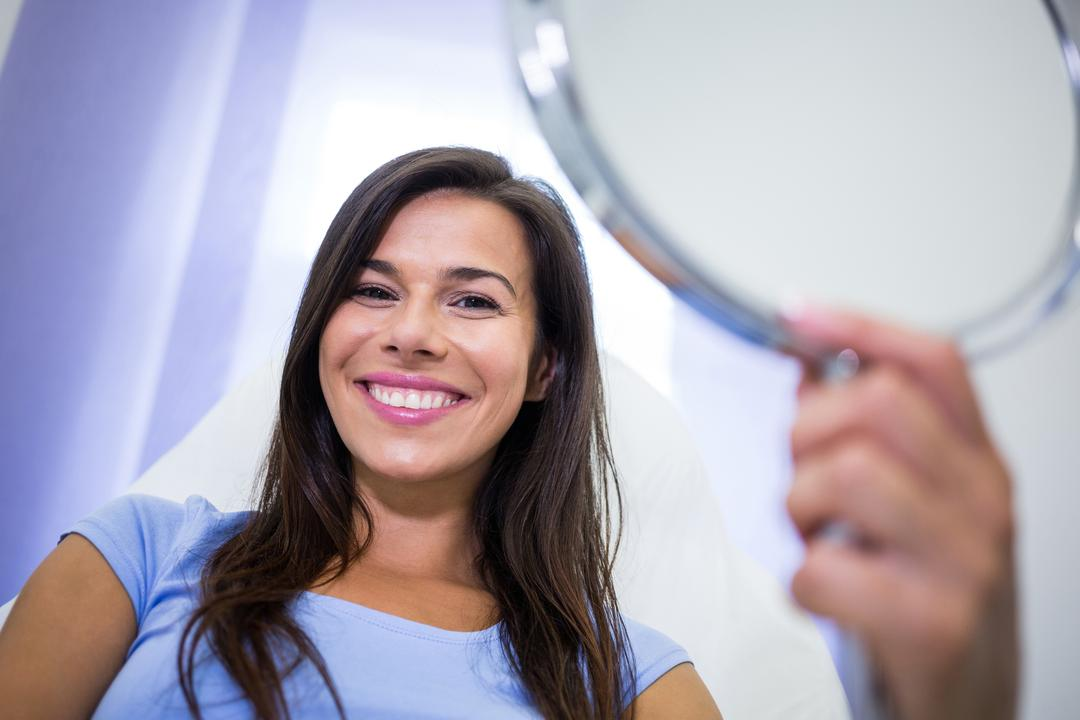 Portrait of smiling patient holding a mirror at clinic