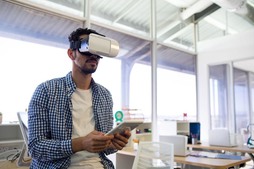 Male executive using virtual reality headset and digital tablet in office