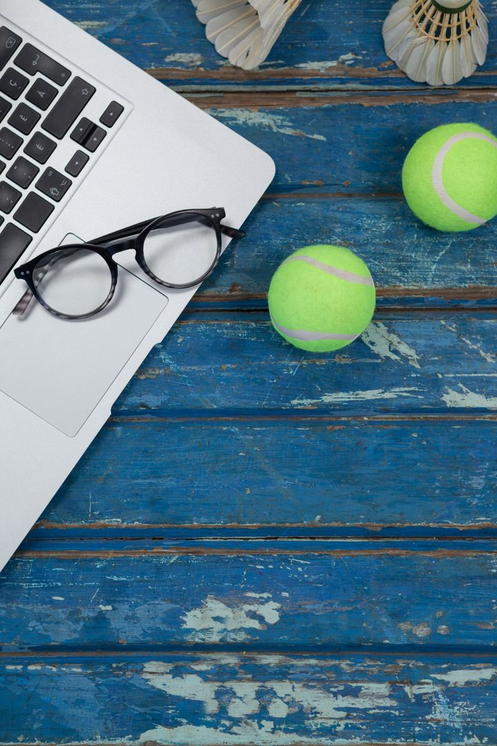 Overhead view of laptop and eyeglasses with shuttlecocks by tennis balls on blue wooden table Free Stock Images from PikWizard