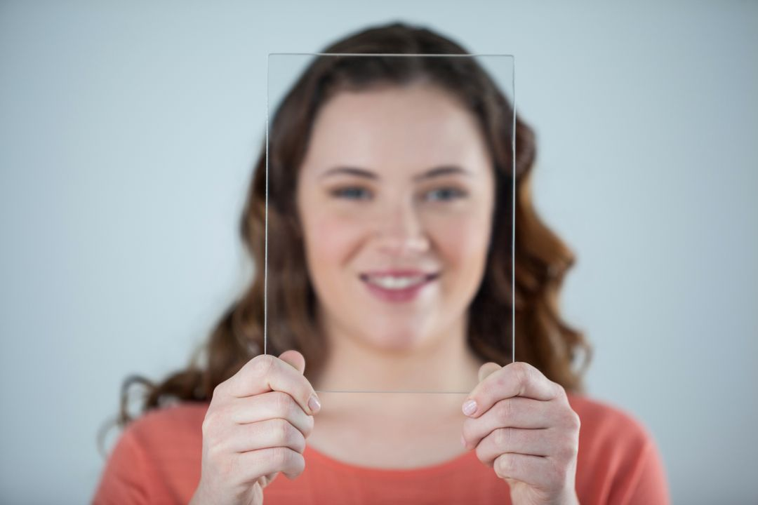 Portrait of smiling woman holding a glass sheet against her face Free Stock Images from PikWizard