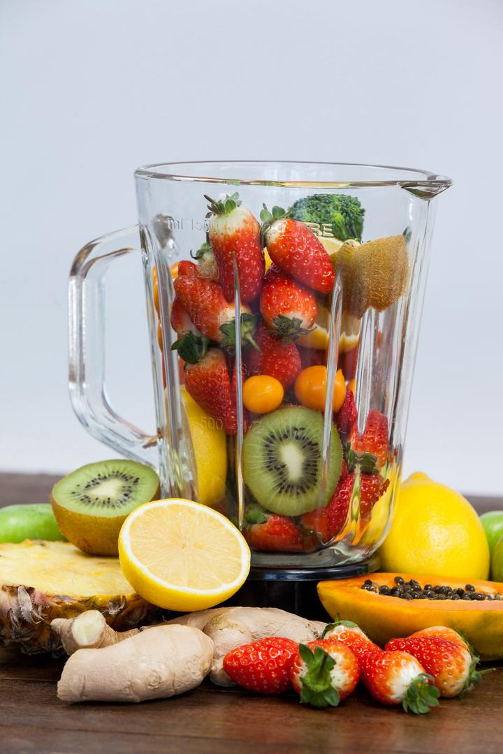 Various fruits and vegetables in blender on table - diet concept